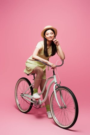 Photo for Happy asian young woman in straw hat riding bicycle and looking away on pink - Royalty Free Image