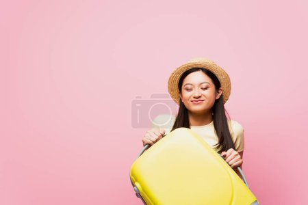 excitado asiático chica con cerrado ojos en paja sombrero celebración equipaje aislado en rosa