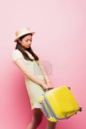 bouleversé asiatique fille en paille chapeau regarder jaune bagages sur rose