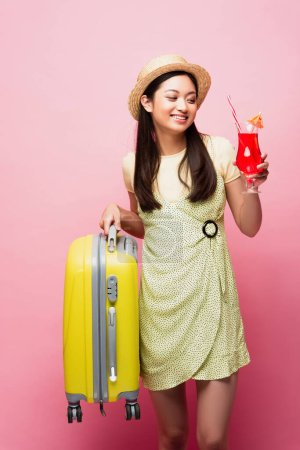 happy asian girl in straw hat holding cocktail and yellow baggage on pink