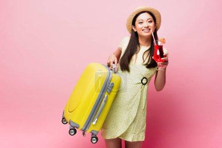 Foto de Sonriente asiático chica en paja sombrero celebración cóctel y amarillo equipaje en rosa - Imagen libre de derechos