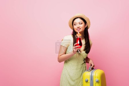 smiling asian woman in straw hat holding cocktail and yellow baggage isolated on pink