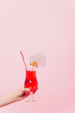 cropped view of woman holding glass with cocktail isolated on pink