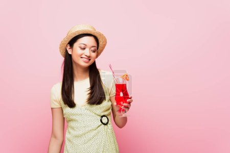 Photo for Smiling young asian woman in straw hat looking at glass with cocktail isolated on pink - Royalty Free Image