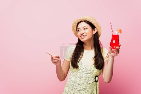 Photo for Smiling young asian woman in straw hat holding glass with cocktail and pointing with finger isolated on pink - Royalty Free Image