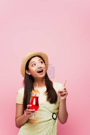 Photo pour Souriant jeune asiatique femme en paille chapeau tenant verre avec cocktail et pointant du doigt tout en regardant isolé sur rose - image libre de droit
