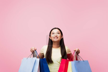 Photo for Cheerful young asian woman looking up while holding shopping bags isolated on pink - Royalty Free Image