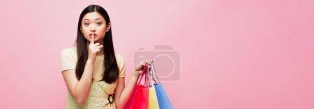 Photo pour Concept horizontal de asiatique fille regarder caméra tout en tenant shopping sacs et montrant silence signe isolé sur rose - image libre de droit