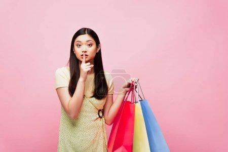 Photo pour Asiatique fille regarder caméra tout en tenant shopping sacs et montrant silence signe isolé sur rose - image libre de droit