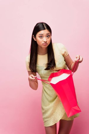 Photo for Disappointed young asian woman holding shopping bag on pink - Royalty Free Image