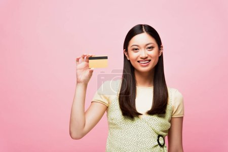 Photo pour Sourire jeune asiatique femme tenant carte de crédit isolé sur rose - image libre de droit