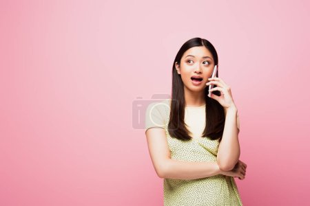 young asian woman with open mouth looking away and talking on smartphone isolated on pink