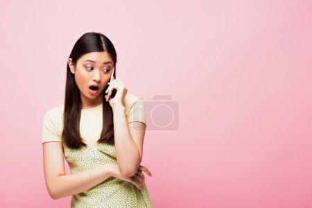 Photo pour Choqué asiatique femme avec bouche ouverte parler sur smartphone isolé sur rose - image libre de droit