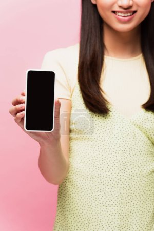 Photo for Cropped view of positive woman holding smartphone with blank screen isolated on pink - Royalty Free Image