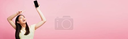 panoramic concept of excited asian woman pointing with finger at smartphone with blank screen isolated on pink