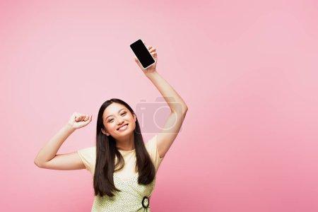 Photo pour Souriant asiatique fille avec serré poing tenant smartphone avec écran vide isolé sur rose - image libre de droit