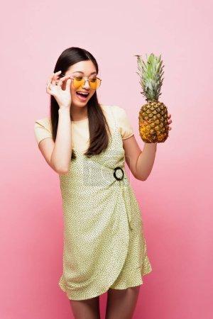 glücklich asiatische Mädchen mit Sonnenbrille Blick auf reife Ananas auf rosa