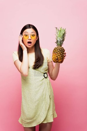 surprised asian girl in sunglasses holding fresh pineapple on pink