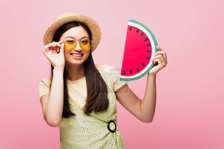 Photo for Cheerful asian girl in straw hat touching sunglasses and holding paper watermelon isolated on pink - Royalty Free Image