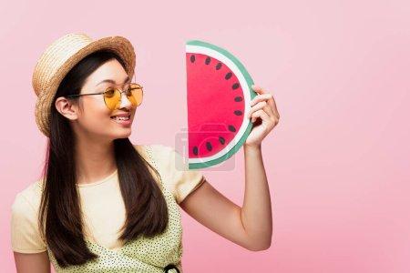 alegre asiático chica en gafas de sol y paja sombrero mirando papel sandía aislado en rosa