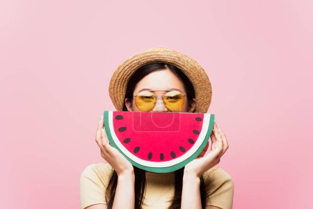 Photo for Asian girl in sunglasses and straw hat covering face with paper watermelon isolated on pink - Royalty Free Image