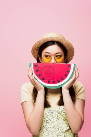 asian woman in sunglasses and straw hat covering face with paper watermelon and looking away isolated on pink