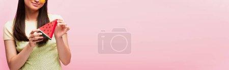 panoramische Ernte positiver Mädchen mit geschnittener Papierwassermelone isoliert auf rosa