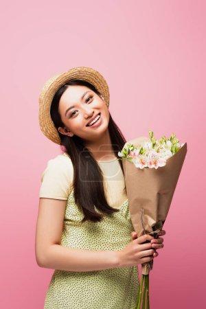 joven asiático mujer en paja sombrero sonriendo y sosteniendo flores aislado en rosa