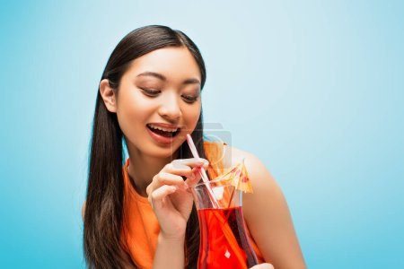 Photo for Cheerful asian girl holding and looking at glass with cocktail on blue - Royalty Free Image