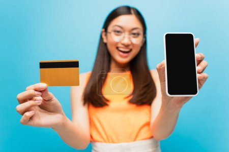 selective focus of happy asian girl holding smartphone with blank screen and credit card isolated on blue