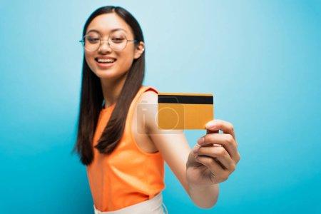 Photo pour Foyer sélectif de sourire asiatique fille dans lunettes tenant carte de crédit sur bleu - image libre de droit