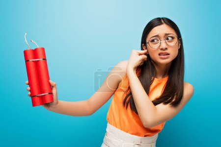 stressed asian girl in glasses covering ear and holding dynamite sticks on blue
