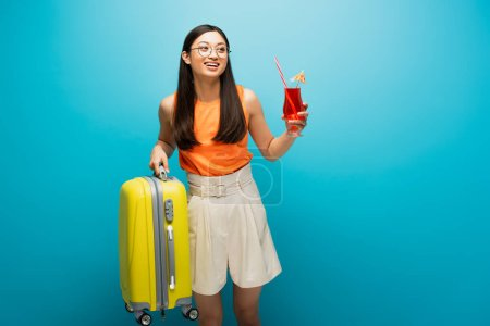 Photo for Happy asian girl in glasses holding cocktail and baggage on blue - Royalty Free Image