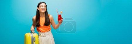 panoramisches Konzept eines glücklichen asiatischen Mädchens in Gläsern mit Cocktail und Gepäck auf blau