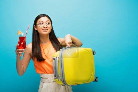 Photo pour Heureux asiatique fille dans lunettes tenue cocktail et bagages tout en regardant loin sur bleu - image libre de droit