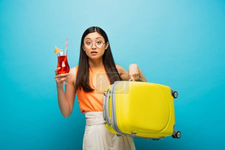 young asian woman in glasses holding baggage and cocktail on blue