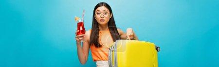 Photo pour Concept panoramique de jolie asiatique femme dans lunettes tenant bagages et cocktail sur bleu - image libre de droit