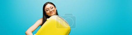 Photo pour Image horizontale de femme asiatique gaie dans des lunettes étreignant bagages jaunes sur bleu - image libre de droit