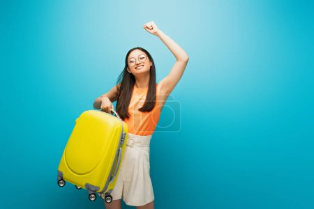 cheerful asian woman in glasses holding yellow luggage and gesturing on blue