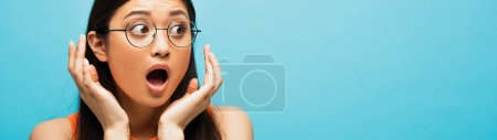 Photo for Horizontal crop of shocked asian woman in glasses gesturing and looking away isolated on blue - Royalty Free Image