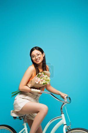 Photo for Cheerful asian girl in glasses riding bicycle and holding flowers on blue - Royalty Free Image