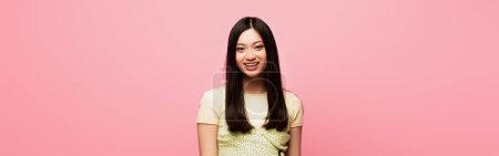 Photo for Horizontal image of positive young asian woman looking at camera and smiling isolated on pink - Royalty Free Image