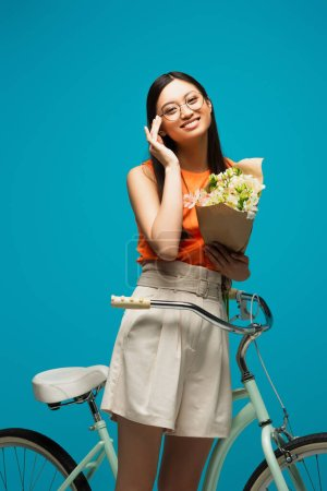 Photo for Happy asian girl in glasses holding flowers near bike isolated on blue - Royalty Free Image