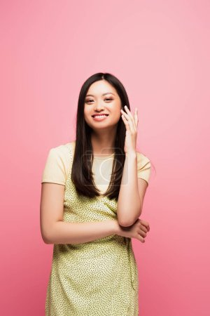 Photo for Happy young asian woman looking at camera and smiling isolated on pink - Royalty Free Image