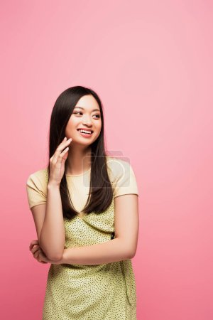 Photo for Happy young asian woman looking away and smiling isolated on pink - Royalty Free Image
