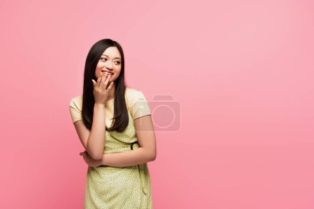 Photo for Happy young asian woman covering mouth isolated on pink - Royalty Free Image