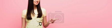 Photo pour Récolte panoramique de gai fille pointant avec doigt isolé sur rose - image libre de droit