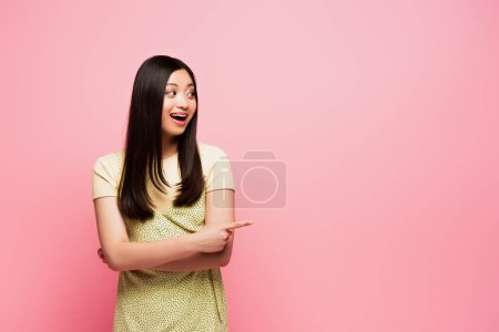 Photo for Excited asian girl pointing with finger and looking away isolated on pink - Royalty Free Image