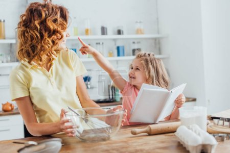 selective focus of girl holding cookbook and pointing with finger at mom holding glass bowl with whisk