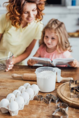 selective focus of chicken eggs, flour in measuring jug and cookie cutters near mother and child reading cookbook